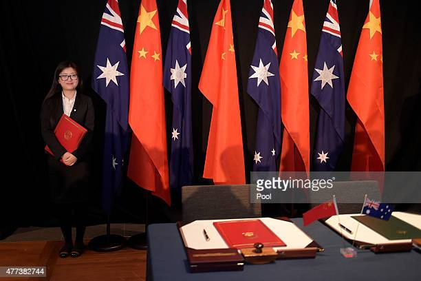 Woman holding a copy of the Free Trade Agreement stands next to National flags of China and Australia during a signing ceremony on June 17, 2015 in...