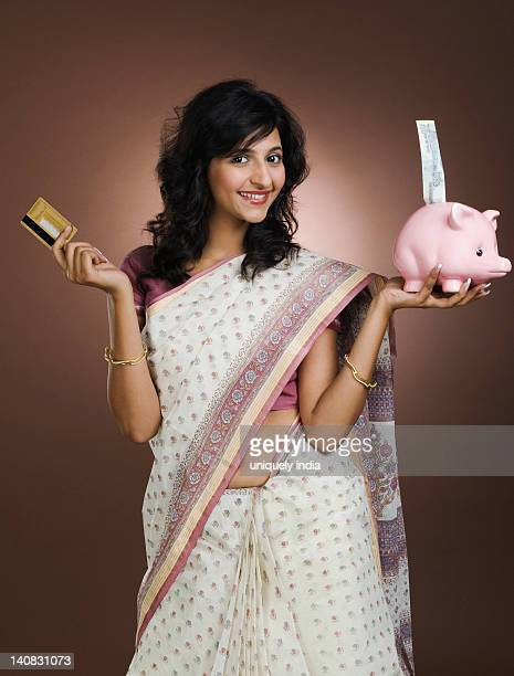 Woman holding a credit card and a piggy bank