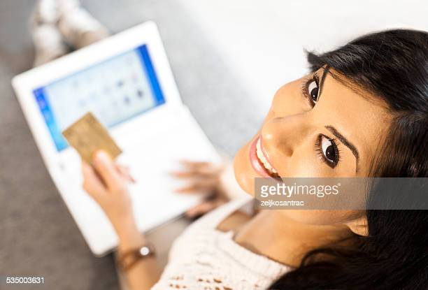 Woman holding a credit card and using computer