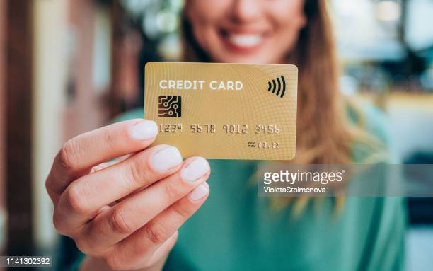 woman holding a credit card - focus on foreground stock pictures, royalty-free photos & images