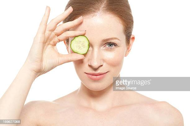 Woman holding a cucumber slice to her eye