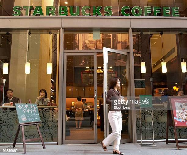 A woman holding a cup of coffee walks out of a Starbucks coffee shop in Tokyo on Wednesday December 22 2004 Japan's demand for services declined in...