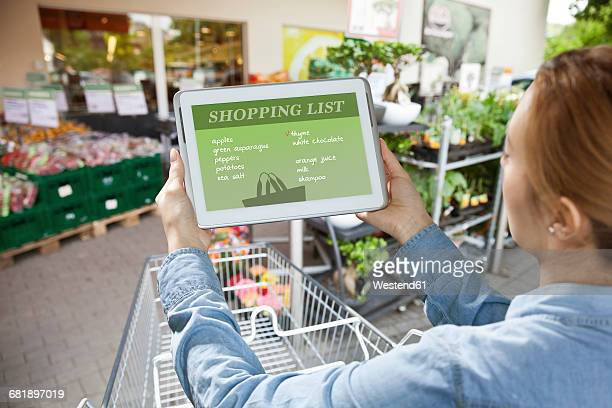 Woman holding a digital tablet with a shopping list in front of a super market