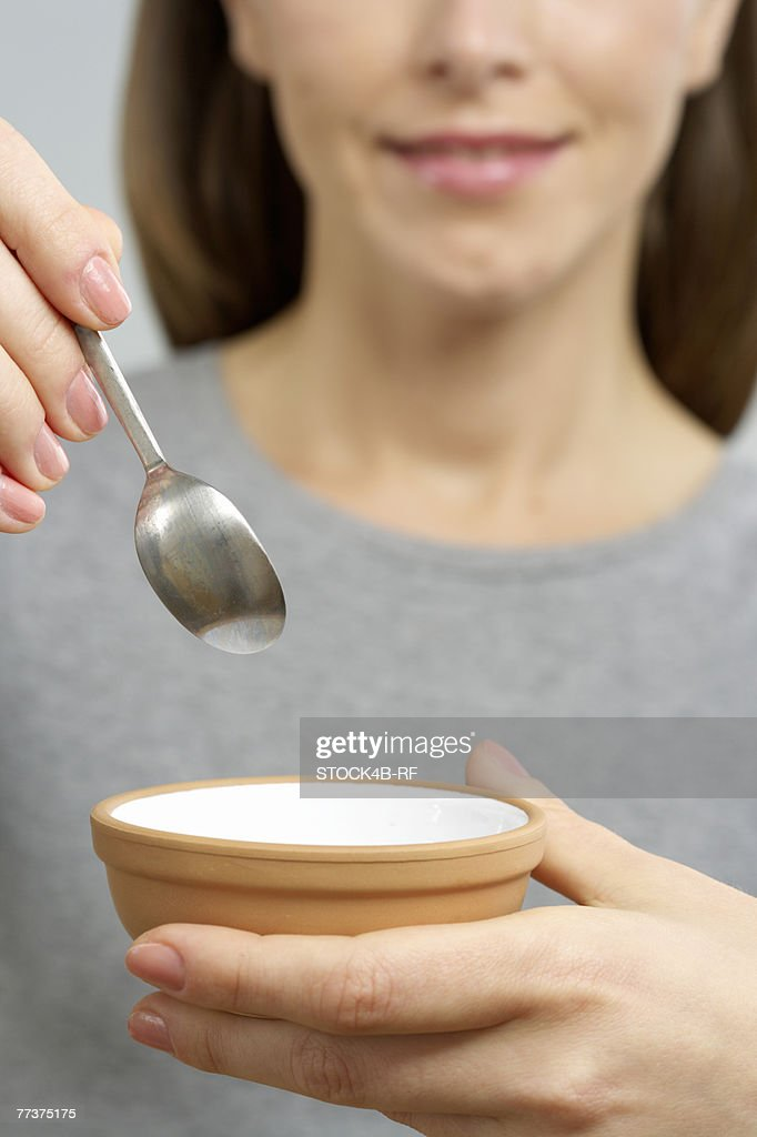 Woman holding a dish and a spoon : Photo