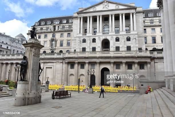 A woman holding a face mask walks past a lone worker sitting to eat lunch on the steps of the Royal Exchange by the Bank of England an area that...