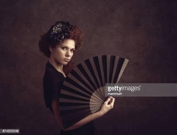 woman holding a fan - 1900s vintage style - mulher fatal imagens e fotografias de stock
