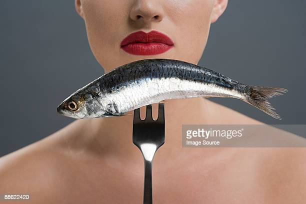 Woman holding a fish on a fork