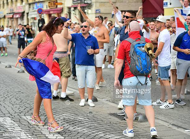 A woman holding a French flag speaks with England fans as they gather in Marseille southern France on June 10 ahead of England's Euro 2016 football...