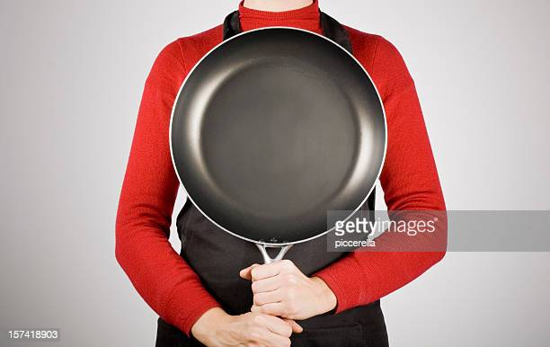 Woman holding a frying pan and not showing her face