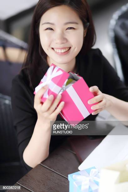 Woman holding a gift box and smiling
