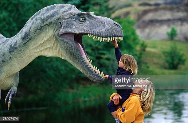 Woman holding a girl up to a dinosaur model, Drumheller Valley, Alberta, Canada, North America