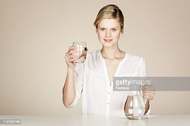 Woman holding a glass and jug of water