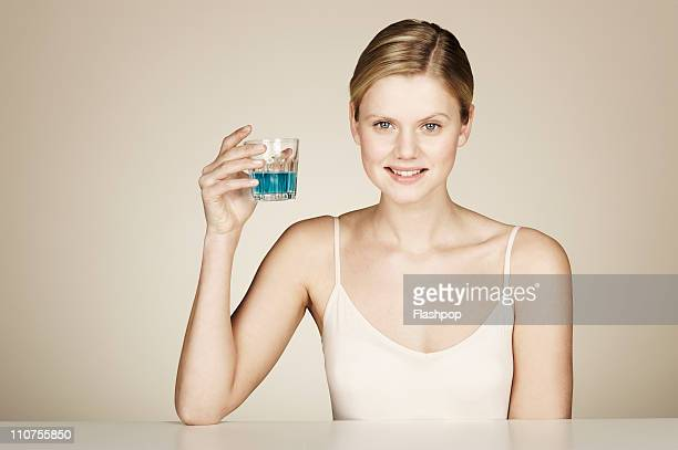 woman holding a glass of mouthwash - mouthwash stock pictures, royalty-free photos & images