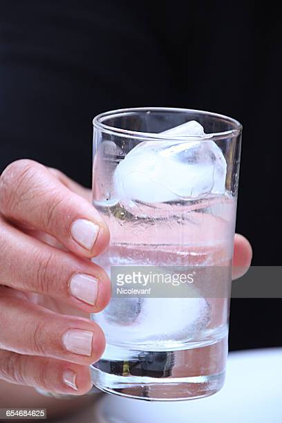 Woman holding a glass of ouzo with ice cubes