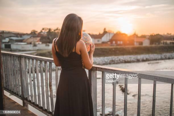 woman holding a globe dreaming about traveling - vestido preto imagens e fotografias de stock