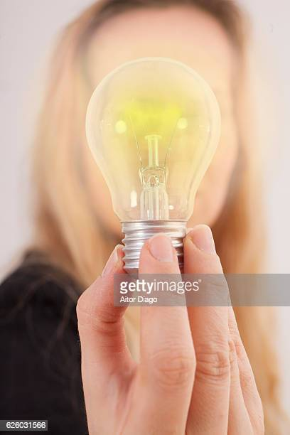 woman holding a glowing bulb with her fingers. - incandescent bulb fotografías e imágenes de stock