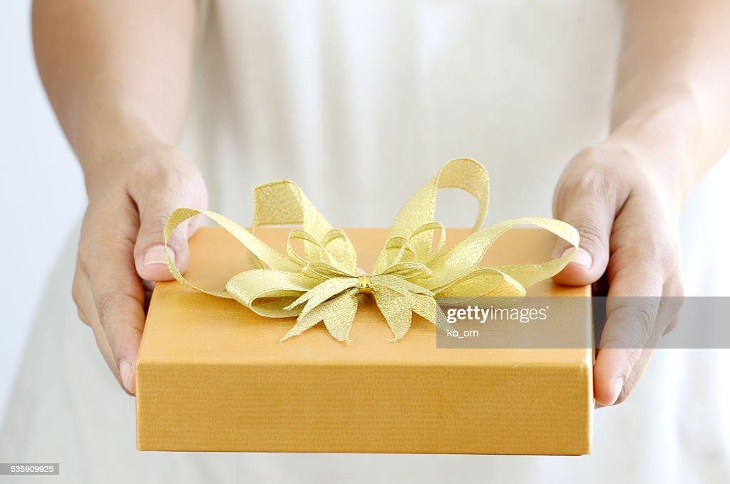 Frau hält ein Geschenk box gold : Stock-Foto