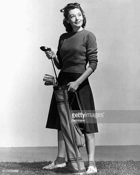 Woman holding a golf club and a golf bag, and a golf ball is lying on the ground. Full length photograph. Ca. 1940s-1950s.