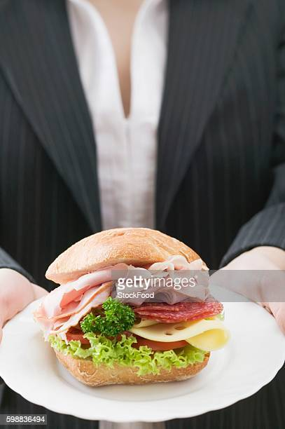 Woman holding a ham and cheese sandwich on a plate
