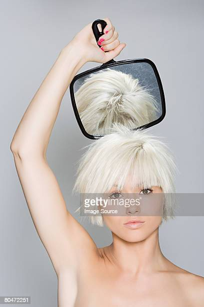 A woman holding a hand mirror