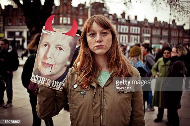 CONTENT] Woman holding a handmade sign showing Margaret Thatcher with blood in the corner of her mouth and devil's horns on the day of Thatcher's...
