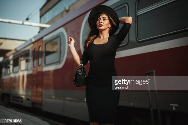 woman holding a hat on a windy day at the railroad station - black dress stock pictures, royalty-free photos & images