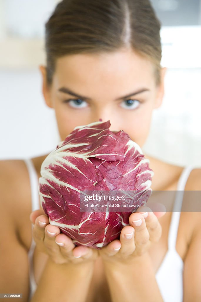 Woman holding a head of radicchio lettuce, partially obscuring her face, looking at camera : Stock Photo