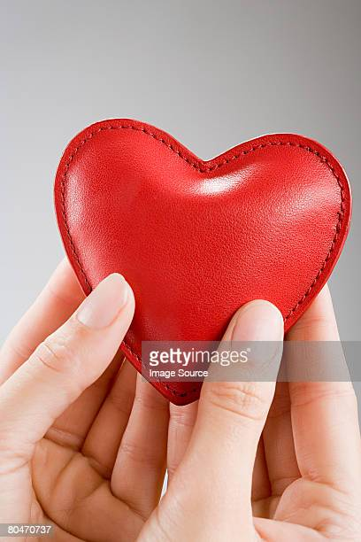 a woman holding a heart cushion - cushion stock photos and pictures
