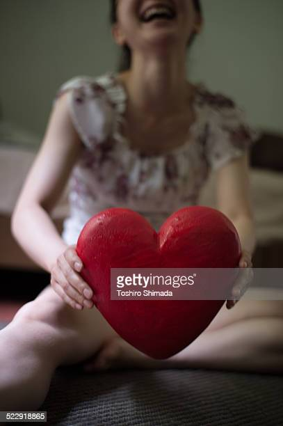 A woman holding a heart shape object