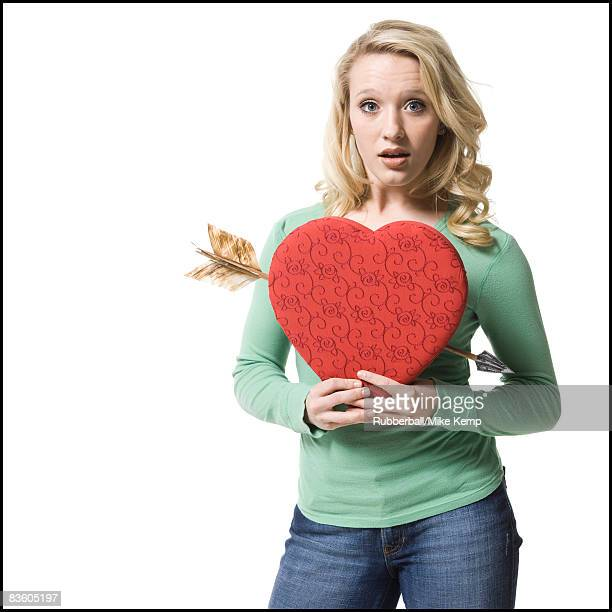 woman holding a heart with an arrow through it