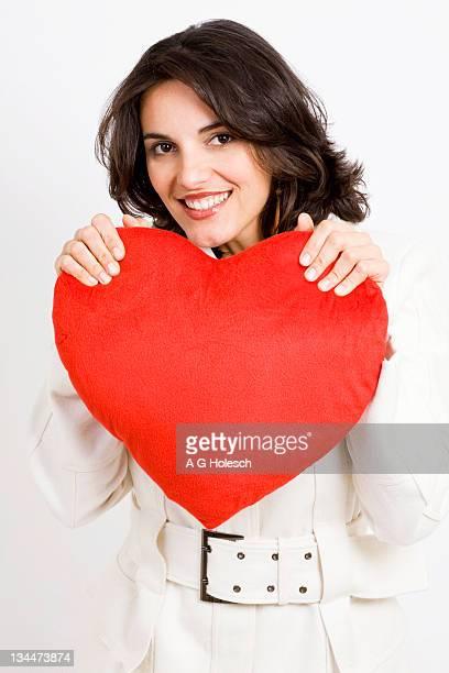 Woman holding a heart-shaped cushion