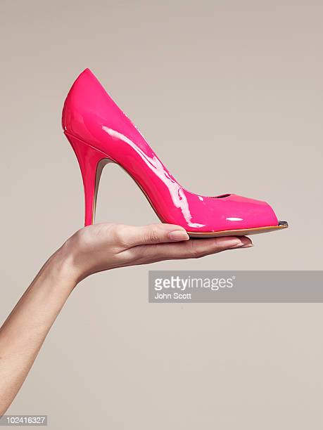 woman holding a high heel shoe - high heels stock pictures, royalty-free photos & images