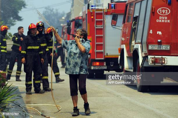 A woman holding a hose to spray water and covering her face with a cloth stands by firefighters during a fire in the village Gornje Sitno near the...