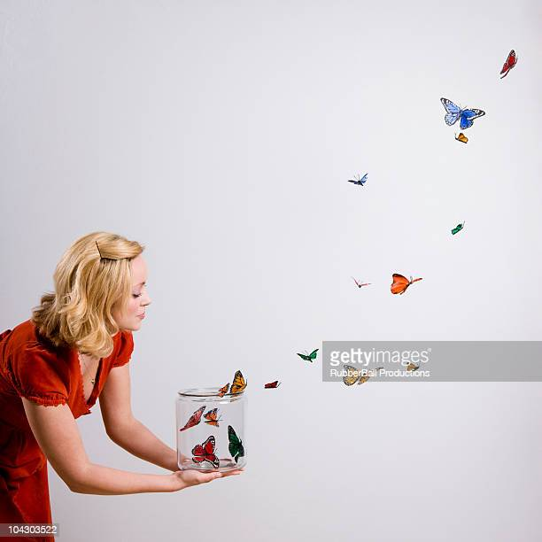 woman holding a jar of butterflies