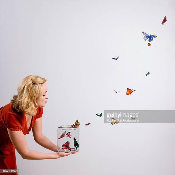 woman holding a jar of butterflies - vlinder stockfoto's en -beelden