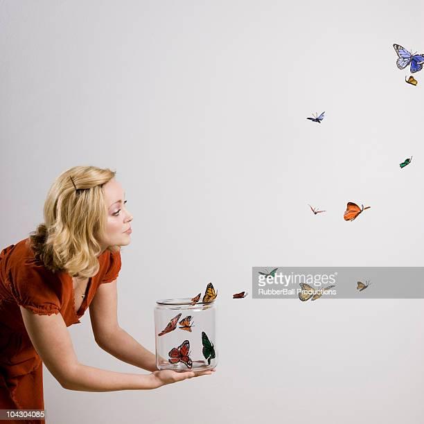 Femme tenant un pot de papillons