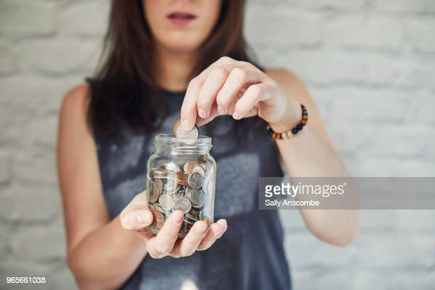 woman holding a jar of money - savings stock pictures, royalty-free photos & images
