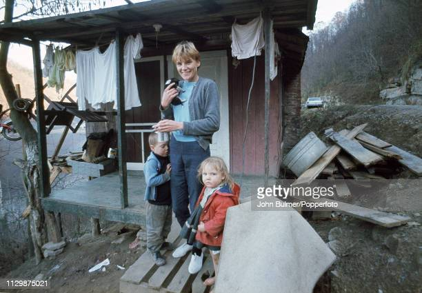 A woman holding a kitty outside a log house with her children Pike County Kentucky US 1967