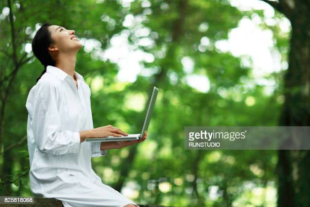 woman holding a laptop and smiling while watching the sky - lush stock pictures, royalty-free photos & images