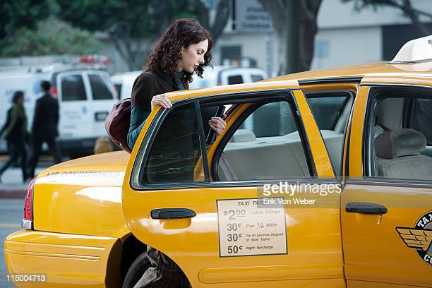woman holding a laptop getting in a taxi - taxi stock pictures, royalty-free photos & images