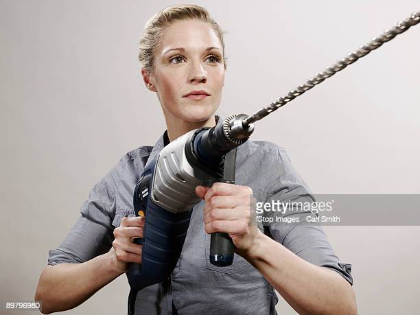 a woman holding a large drill - drill stock pictures, royalty-free photos & images