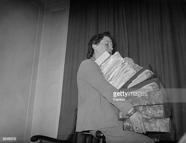 Woman holding a large pile of files and papers.