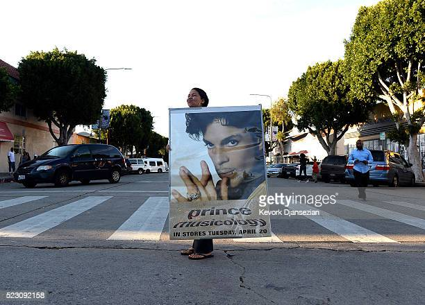 A woman holding a large poster of Prince arrives to a gathering in Leimert Park in memory of musician Prince on April 21 in Los Angeles California...