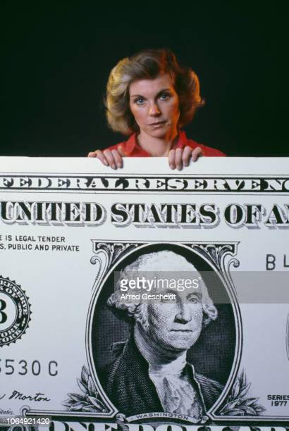 A woman holding a large size print of an American dollar banknote US 1980