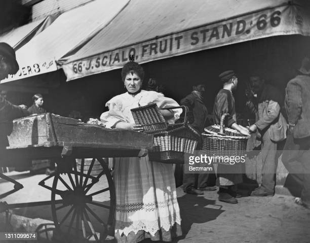 Woman holding a large wicker basket buying from a pushcart vendor in a market on Mulberry Street in the borough of Manhattan in New York City, New...