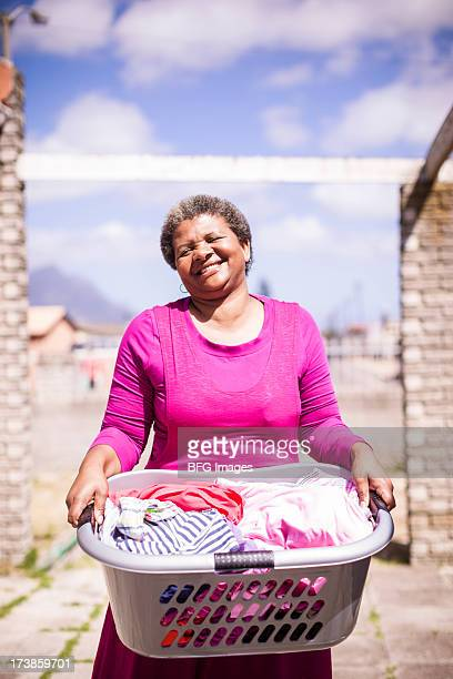 Woman holding a laundry basket, Cape Town, South Africa
