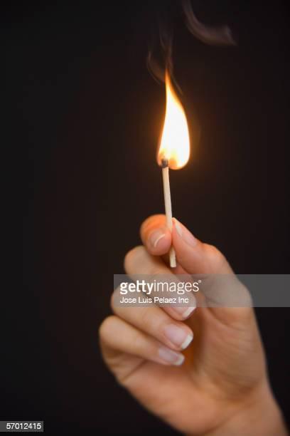 Woman holding a lit match