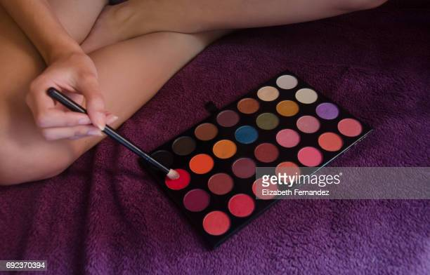 Woman holding a makeup brush over an eyeshadow palette.