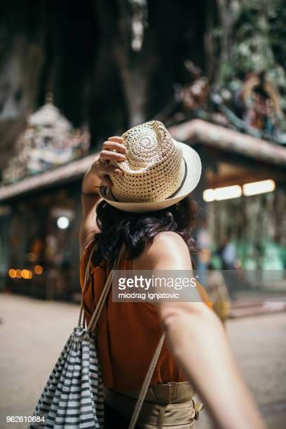 Woman holding a man's hand inside of the Batu caves