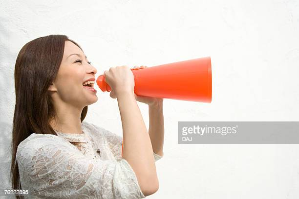 A woman holding a megaphone, side view, white background